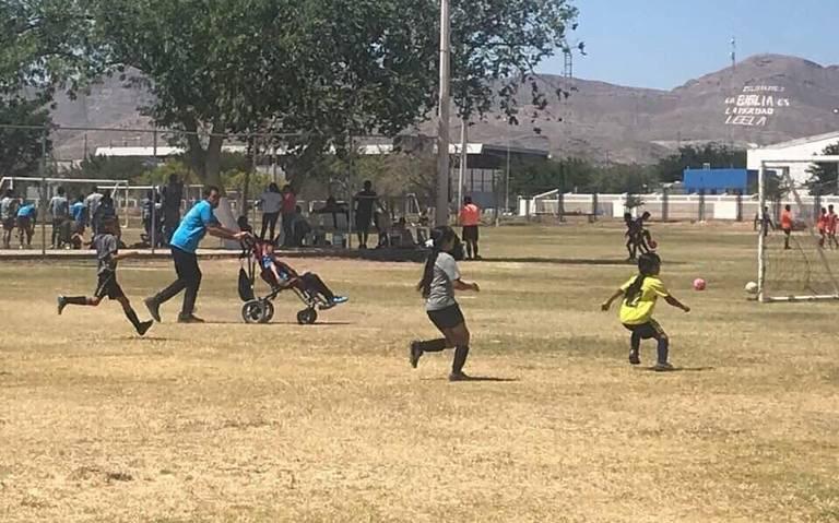 Papá empuja silla de ruedas de su hijo para que juegue fútbol