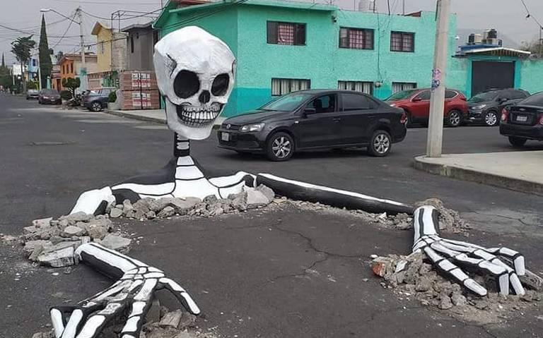 ¡Salen las calaveras! Tapan baches con esqueletos gigantes en Tláhuac