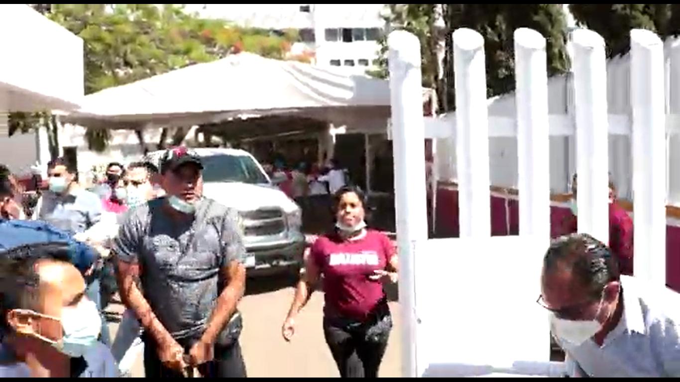 Escolta de Nancy Ortiz Cabrera, delegada de Oaxaca, desenfunda arma durante protestas por falta de vacunas