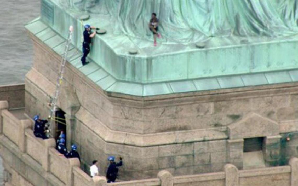 [Video] Rescatan a mujer que escaló la estatua de la libertad para protestar contra ICE