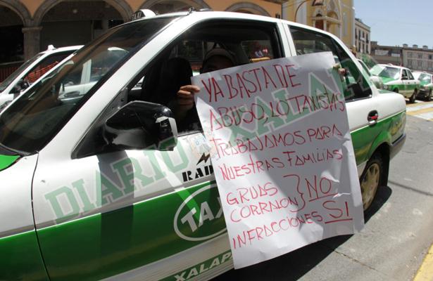Taxistas marchan en contra de abusos de grúas, en Xalapa