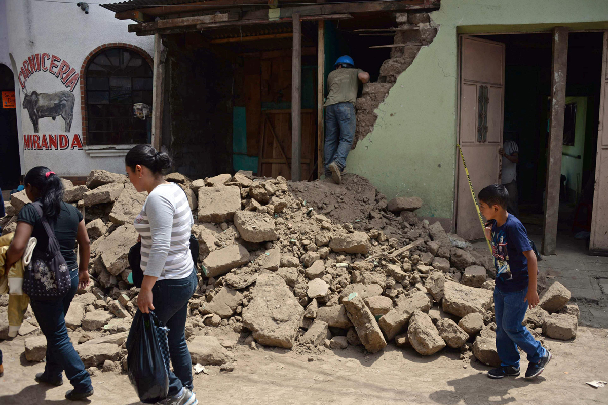 People walk by a house damaged by an earthquake, in San Pedro municipality, San Marcos departament, 240 km from Guatemala City, on July 7, 2014. A strong 6.9-magnitude earthquake rocked parts of southern Mexico and Guatemala on Monday, killing at least two people and injuring more than 40 others. The US Geological Survey said the quake -- initially measured at a magnitude of 7.1 -- struck the Pacific coast of Mexico's Chiapas state at about 1124 GMT at a depth of 60 km. The epicenter was located just two km from the Mexican town of Puerto Madero, and 200 km from Guatemala City. AFP PHOTO / Johan ORDONEZ