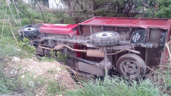 Localizan camioneta volcada entre la maleza