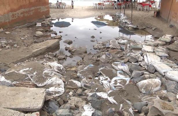 Denuncian vecinos laguna de aguas negras en acceso de playa La Ropa