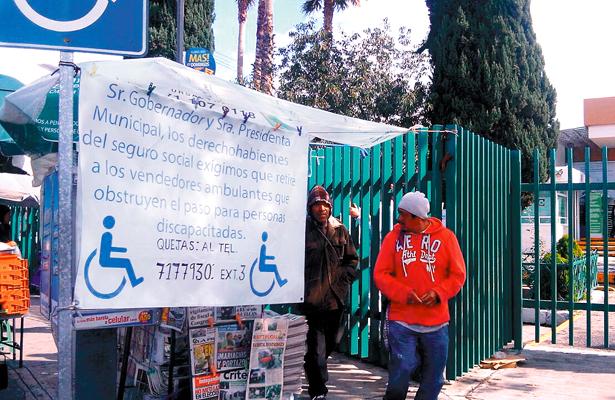 PACIENTES de la clínica del IMSS colocaron una manta solicitando a las autoridades competentes el retiro de vendedores ambulantes a las puertas del hospital.  Foto: El Sol de Hidalgo.