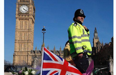 Un oficial de policía pasa arreglos florales para las víctimas del ataque terrorista en la explanada del Parlamento británico el pasado 22 de marzo, en Londres, Inglaterra.