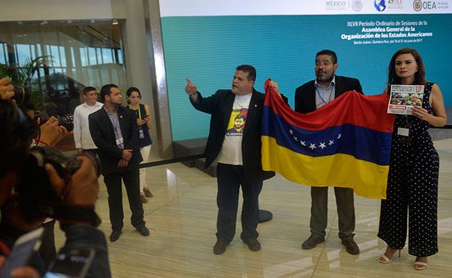 En Cancún, Quintana Roo, durante la tercera sesión plenaria de la 47 Asamblea General de la OEA, un grupo de ocho personas irrumpieron para exigir apoyo para el pueblo venezolano; los inconformes gritaron consignas contra el presidente venezolano Nicolás Maduro / Foto: AFP