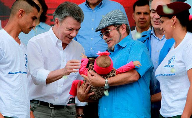 El presidente de Colombia, Juan Manuel Santos saluda a una bebé que es sostenida por el máximo líder de las FARC, Rodrigo Londoño, alias Timochenko. Foto: EFE