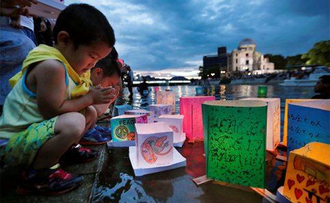 Niños rezan después de lanzar linternas de papel en el rió Moyotasu. Foto: Reuters