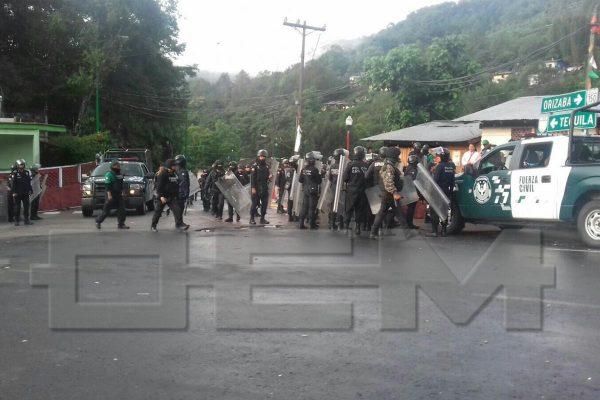 Inconformes queman dos casas, tiran portón de alcalde, dañan patrulla, agreden a policías y detienen a agresor.