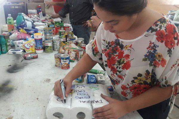 Escriben mensajes y frases de apoyo en latas y víveres para los damnificados