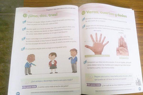 Mano con 6 dedos en libro de matemáticas, de segundo año