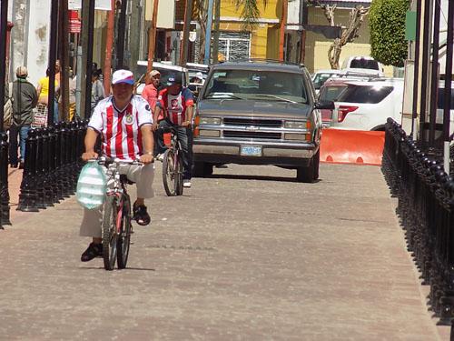 Transitan bicicletas y motos sobre la calle Carranza