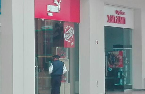 """UN VIGILANTE observa al interior de la joyería """"Puma Time"""" ubicada en Plaza Galería, que fue asaltada ayer por dos jóvenes que tras el ilícito huyeron."""