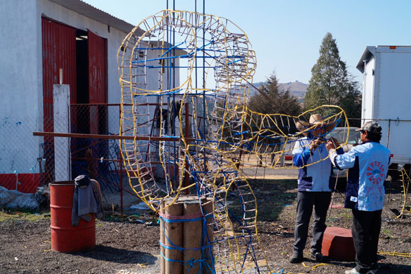 Tras una ardua jornada de trabajo, los artesanos exponen una pieza terminada, la cual será montada en una torre metálica que forma parte de la estructura de un castillo pirotécnico. / Manuel MORALES