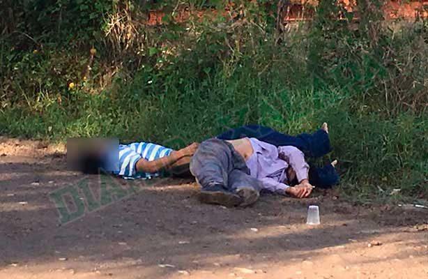 Tiran dos cadáveres en un camino de terracería