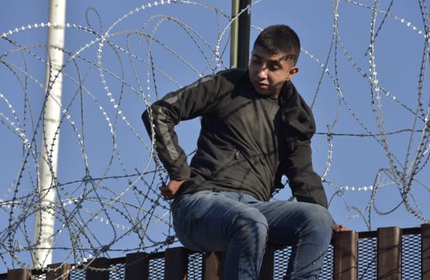 Rescata policía y bomberos a un adolescente que quedó atrapado entre púas en lo alto de cerco fronterizo