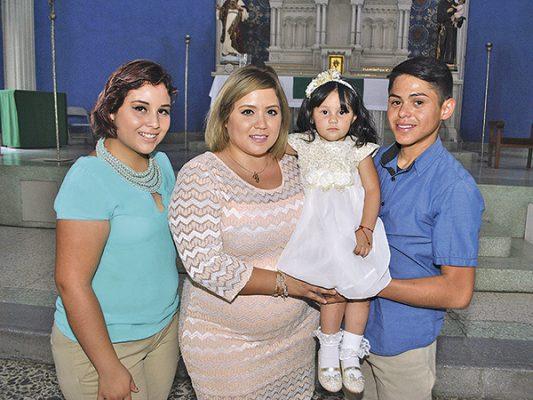 La pequeña con papás y madrina.