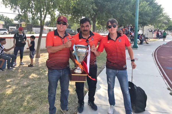 Esta es la copa obtenida por el conjunto de El Calor, la sostienen Esteban y Timothy Tolman así como el director técnico del equipo, Ricardo López.