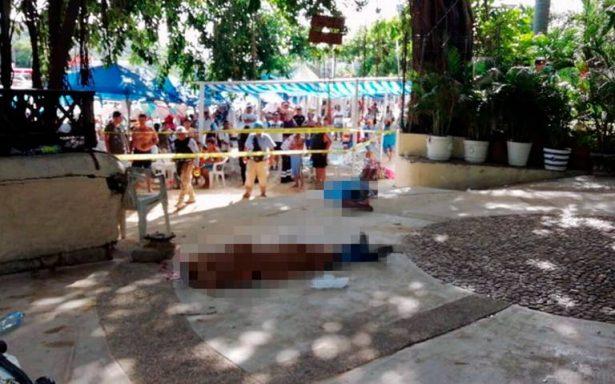 Turistas descansan junto a cadáveres de dos hombres